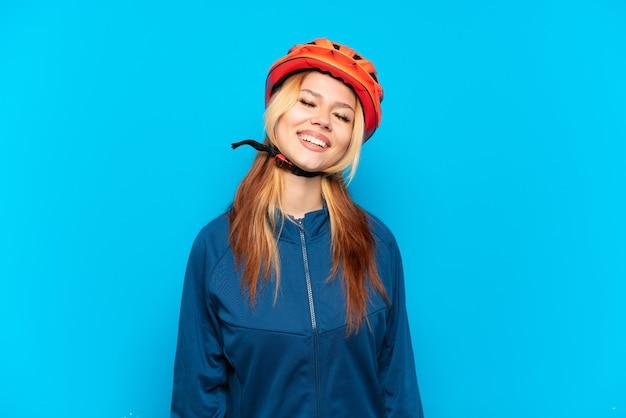 Jovem ciclista isolada em um fundo azul rindo