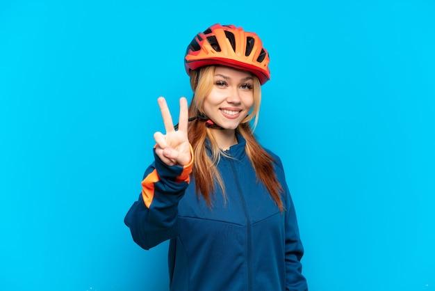 Jovem ciclista isolada em um fundo azul sorrindo e mostrando sinal de vitória