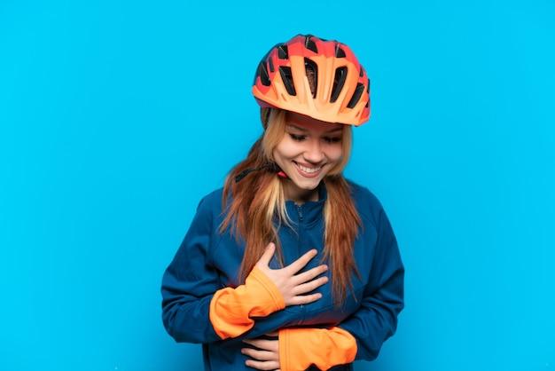 Jovem ciclista isolada em um fundo azul sorrindo muito