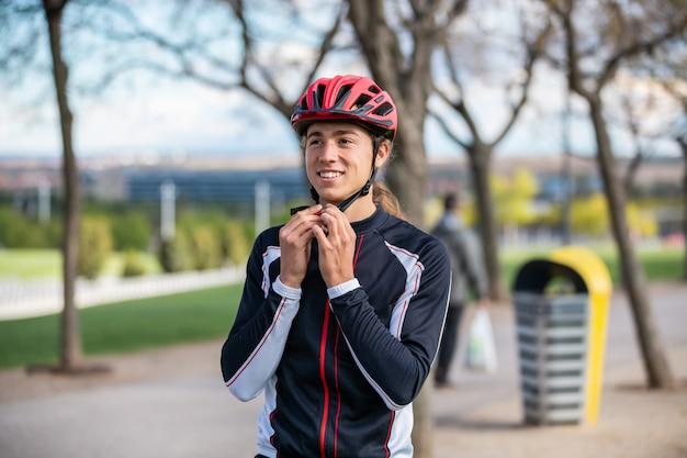 Jovem ciclista masculina bonita no sportswear dobrar capacete protetor no parque da cidade bonita