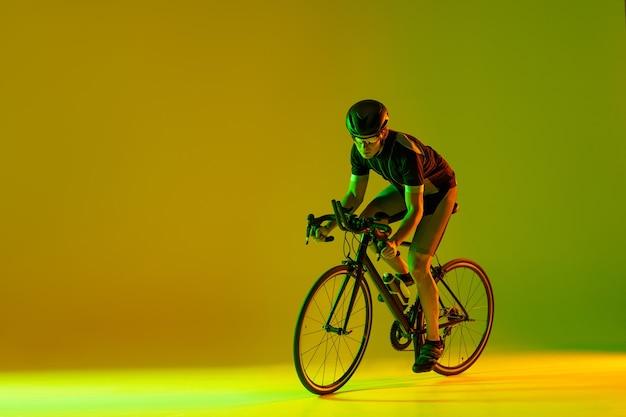 Jovem ciclista masculino de bicicleta isolado na parede amarela verde gradiente em homem de néon treinando e praticando
