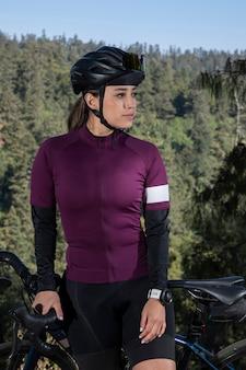 Jovem ciclista posando com sua bicicleta em um mirante com uma paisagem arborizada ao fundo