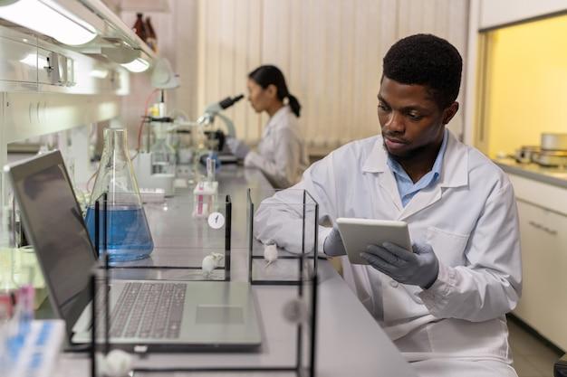 Jovem cientista africano usando tablet digital e examinando dois tipos de ratos nas caixas no laboratório