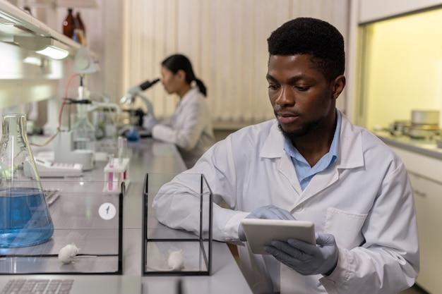 Jovem cientista de etnia africana olhando ratos em caixas de vidro e usando um tablet