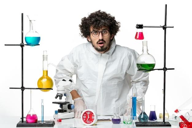 Jovem cientista do sexo masculino em terno especial branco posando de frente