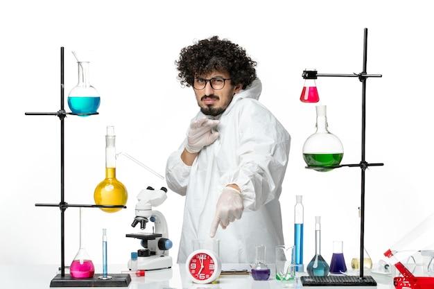 Jovem cientista do sexo masculino em um terno branco especial dentro da sala com soluções