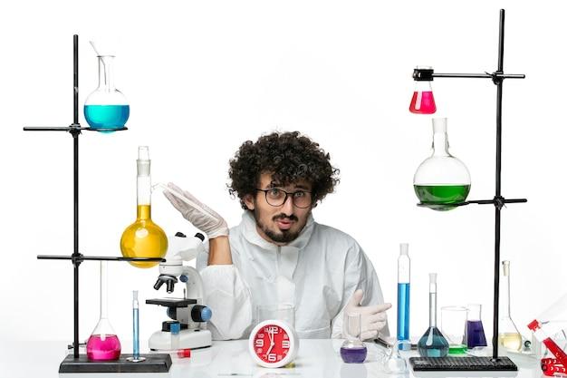 Jovem cientista do sexo masculino em um terno especial branco de frente para trabalhar com soluções