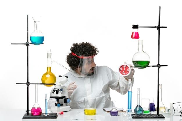 Jovem cientista do sexo masculino em um terno especial com capacete protetor segurando o relógio na parede branca do laboratório de ciências covid - homem de química