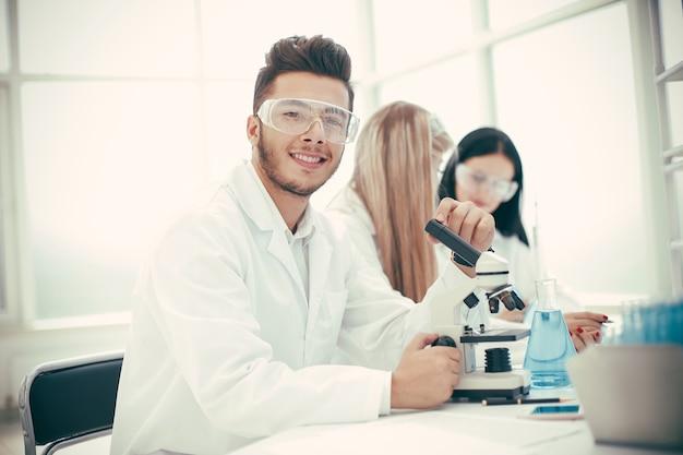 Jovem cientista e seus assistentes testando uma vacina contra o coronavírus. ciência e saúde