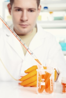 Jovem cientista energético carrega amostra de líquido laranja em um tubo