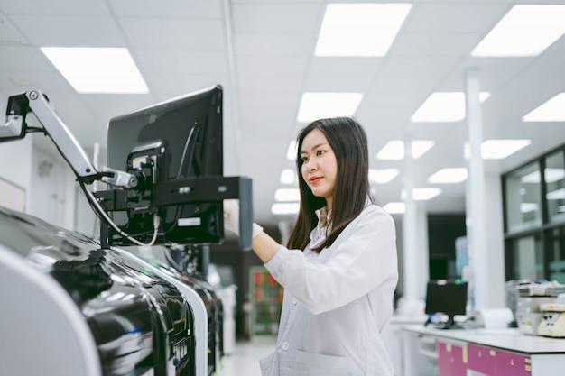 Jovem cientista feminina observe os resultados do relatório do analisador de sangue de automação no laboratório médico