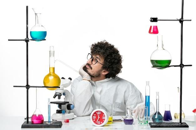 Jovem cientista masculino em traje especial a sonhar na parede branca de frente