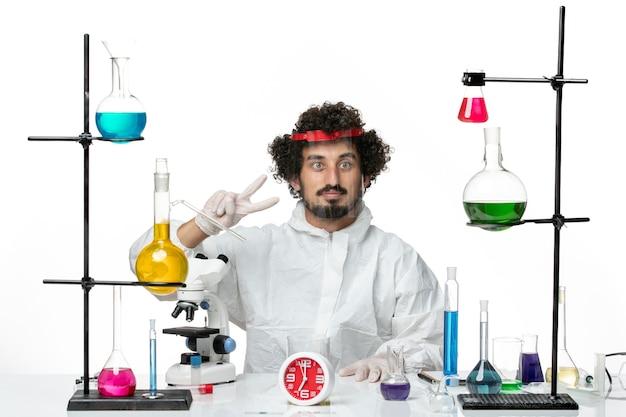 Jovem cientista masculino em um terno especial, usando capacete protetor e trabalhando na parede branca de frente