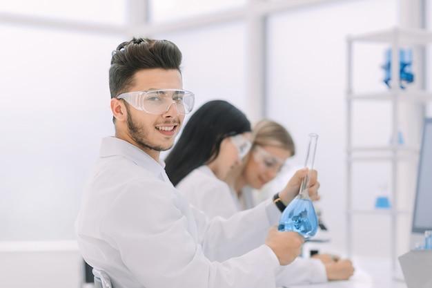 Jovem cientista mostra um copo com líquido. ciência e saúde
