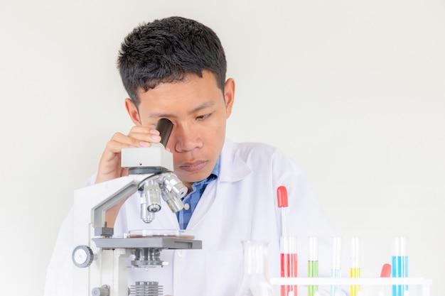 Jovem cientista olhando através de um microscópio em um laboratório
