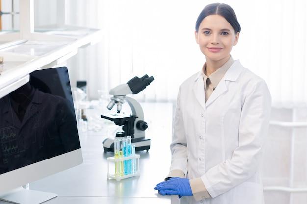 Jovem cientista ou farmacêutica bem-sucedida de luvas e avental branco, parada no local de trabalho com microscópio em laboratório