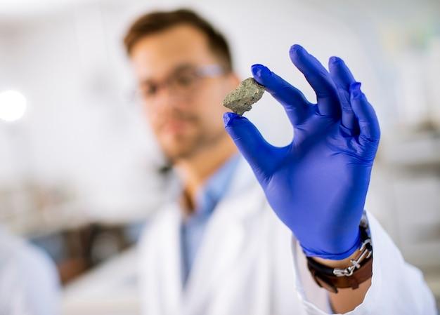 Jovem cientista segura um espécime mineral em uma luva protetora azul no laboratório de ciências materiais