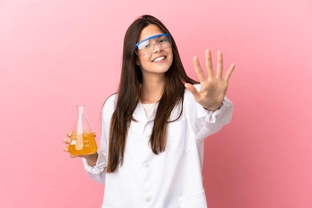 Jovem cientista sobre fundo rosa isolado, contando cinco com os dedos