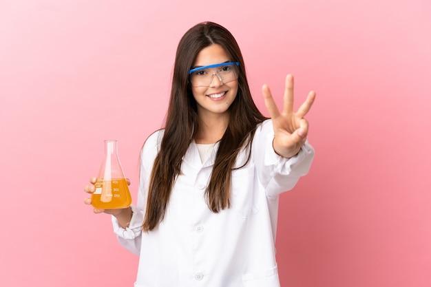 Jovem cientista sobre fundo rosa isolado feliz e contando três com os dedos