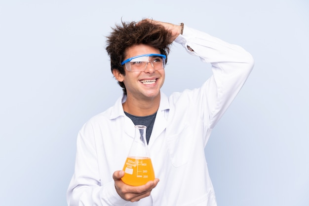 Jovem cientista sobre parede azul isolada rindo