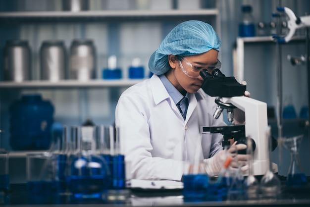 Jovem cientista trabalhando com um microscópio em um laboratório. jovem cientista fazendo alguma pesquisa.