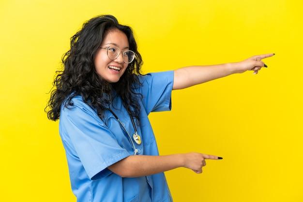 Jovem cirurgiã mulher asiática isolada em fundo amarelo apontando o dedo para o lado e apresentando um produto