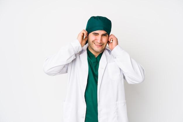 Jovem cirurgião cobrindo os ouvidos com as mãos