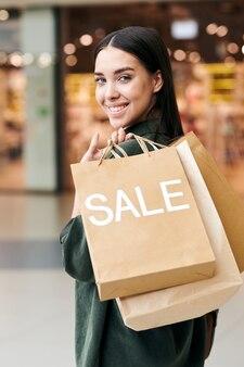 Jovem cliente alegre carregando um monte de sacos de papel enquanto se move ao longo de um grande centro comercial contemporâneo e olha para a câmera