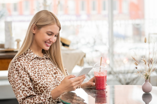 Jovem cliente alegre com o smartphone percorrendo as mensagens enquanto está sentada à mesa no café e bebendo