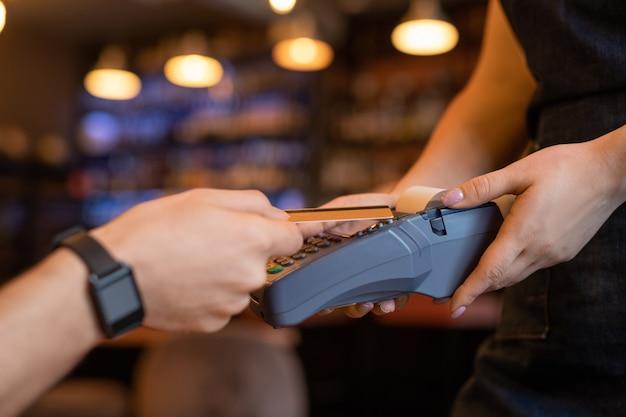 Jovem cliente contemporâneo segurando um cartão de plástico sobre o terminal de pagamento nas mãos de uma garçonete enquanto paga por uma bebida ou almoço em um restaurante