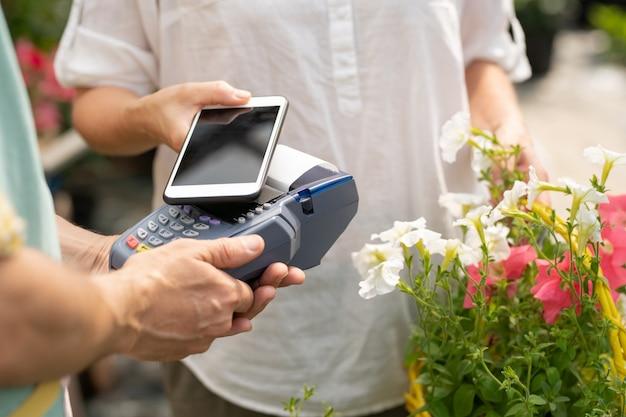 Jovem cliente de floricultura ou centro de jardim segurando smartphone sobre a máquina de pagamento enquanto compra flores