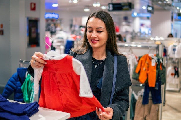 Jovem cliente escolhendo roupas de bebê ou roupas infantis na loja. comprando na loja para crianças pequenas