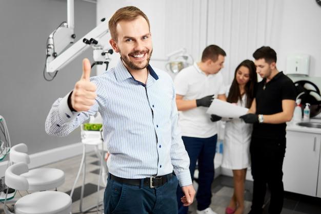 Jovem cliente masculino atraente de uma odontologia está sorrindo para a câmera e mostrando polegares para cima sendo feliz após o tratamento. três especialistas em odontologia estão discutindo algo em segundo plano.