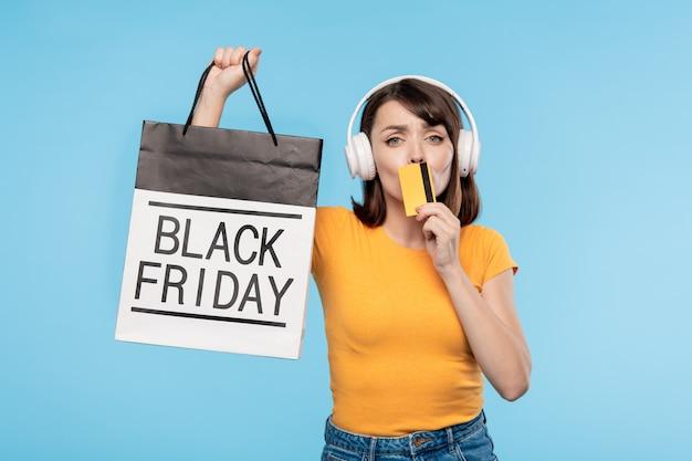 Jovem cliente rico com um cartão de crédito mostrando a você um saco de papel após a liquidação na sexta-feira negra, enquanto está isolado