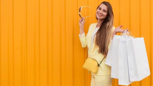 Jovem cliente vestindo roupas amarelas em fundo laranja