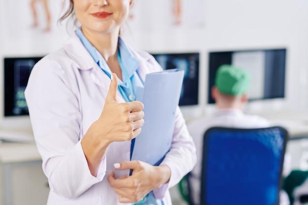 Jovem clínica geral positiva com pasta de documentos nas mãos mostrando o polegar para cima