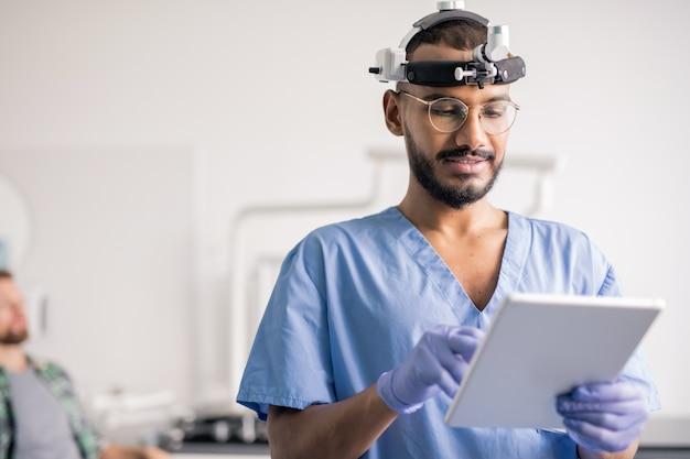 Jovem clínico de uniforme e equipamento médico na cabeça usando o touchpad enquanto rola os dados online no hospital