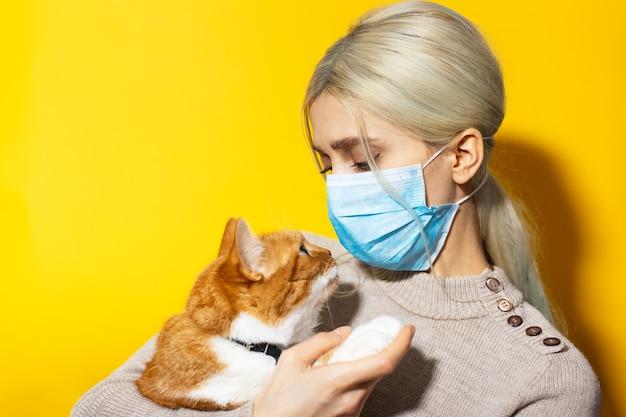 Jovem close-up, veterinário com gato branco vermelho nas mãos, usando máscara médica na parede amarela. olhem nos olhos um do outro.