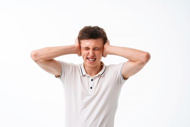 Jovem cobre a cabeça e os ouvidos com as mãos