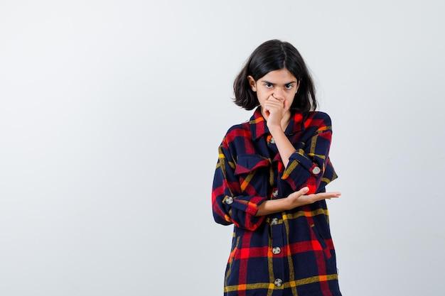 Jovem, cobrindo a boca com a mão enquanto estica a mão para segurar algo na camisa e olhando séria, vista frontal.