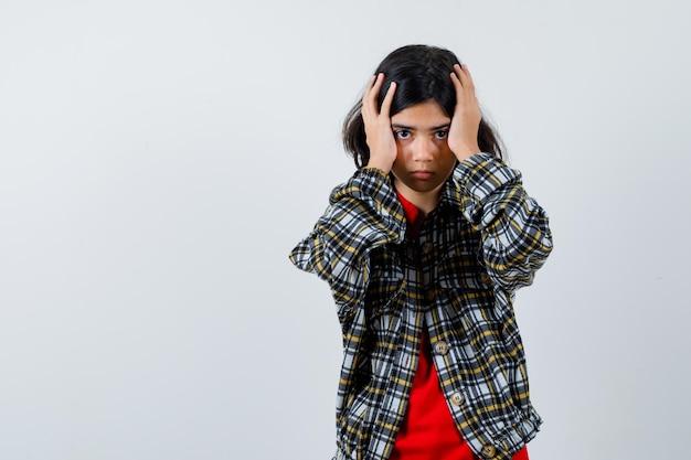 Jovem, cobrindo a cabeça com as mãos em camisa xadrez e camiseta vermelha e olhando séria, vista frontal.