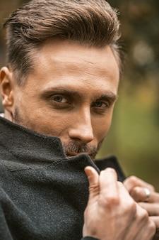 Jovem cobrindo o rosto com uma ponta do casaco parado na rua com um casaco de outono sorrindo