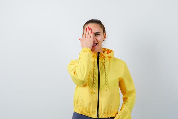 Jovem, cobrindo os olhos com a mão na jaqueta amarela e olhando positiva, vista frontal.