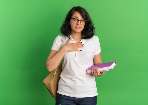 Jovem colegial bonita caucasiana em choque com óculos e bolsa traseira coloca a mão no peito segurando livros verdes com espaço de cópia
