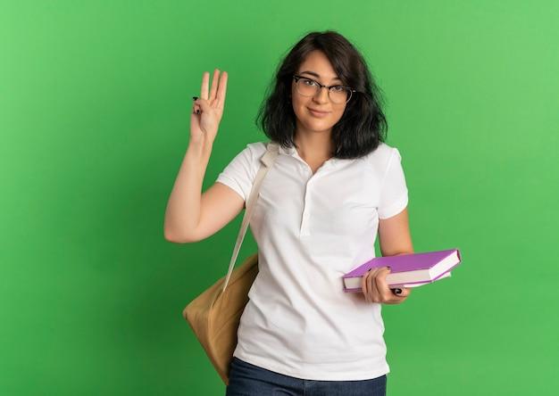 Jovem colegial, bonita e confiante, caucasiana, usando óculos e mochila, gesticula três segurando livros em verde com espaço de cópia