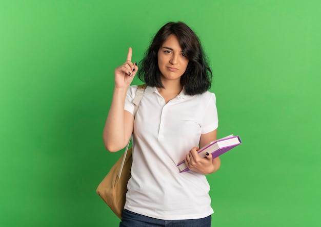 Jovem colegial caucasiana irritada com uma bolsa nas costas apontando para cima segurando livros em verde com espaço de cópia