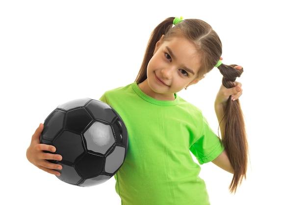 Jovem colegial com uma bola de futebol multicolor nas mãos isoladas em branco