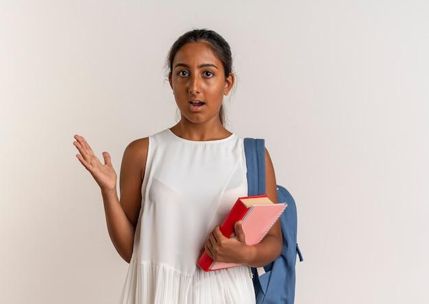 Jovem colegial impressionada usando mochila segurando o livro com o caderno e mostrando com a mão ao lado