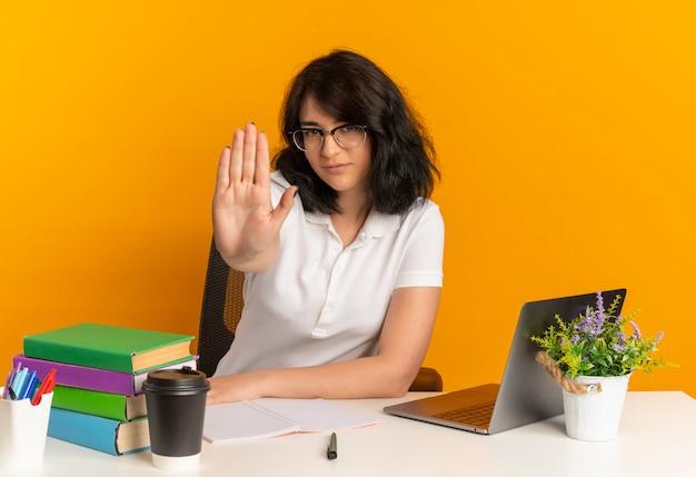 Jovem colegial, muito confiante, caucasiana, de óculos, sentada à mesa com gestos de ferramentas da escola, pare de sinal com a mão na laranja com espaço de cópia