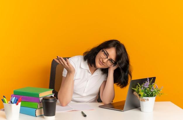 Jovem colegial, muito confiante, caucasiana, de óculos, sentada na mesa com ferramentas escolares, coloca a cabeça na mão isolada no espaço laranja com espaço de cópia